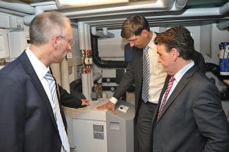 Andreas Klapdor und Dr. Norbert Verweyen (beide RWE) mit dem Minister für Bauen und Wohnen in NRW, Michael Groschek (von links) im Technikraum des Effizienzhauses an der STIEBEL-ELTRON-Wärmepumpe. (Foto: STIEBEL ELTRON)